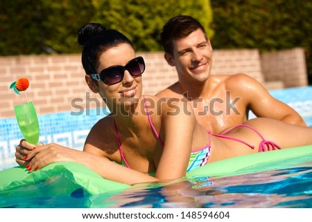 Young people in swimming pool at summertime, smiling.