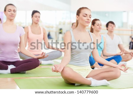 Young people in the lotus position - stock photo