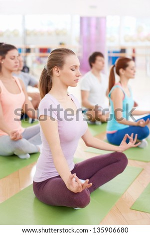 Young people in the lotus position in fitness club - stock photo