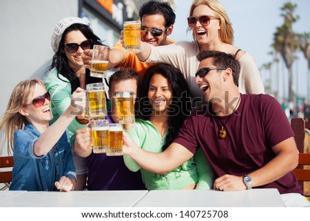 Young People in their twenties on the Venice Beach boardwalk in California drinking beer - stock photo