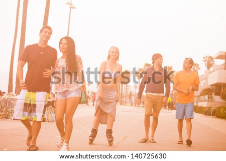 Young People in their twenties walking and roller blading on the Venice Beach boardwalk - stock photo