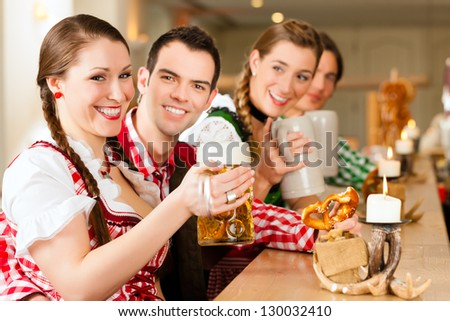 Young people in traditional Bavarian Tracht in restaurant or pub with beer and steins - stock photo