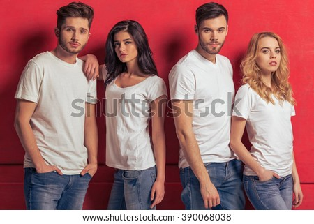 Young people in white t shirts and jeans are looking at camera, standing against red background