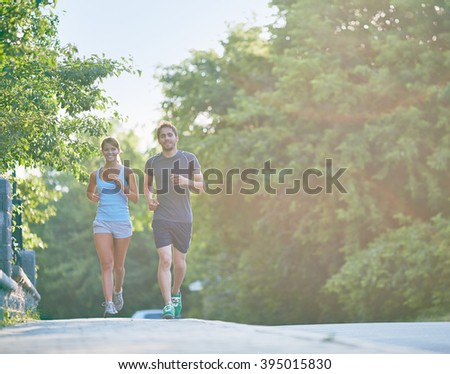 Young people jogging outdoors - stock photo