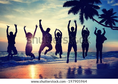 Young People Jumping with Excitement on a Beach - stock photo
