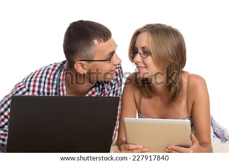 Young people kiss each other, holding laptop and tablet PC - stock photo