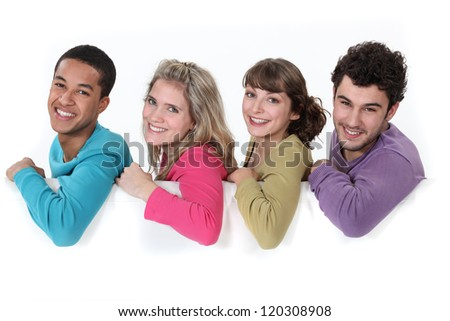 Young people leaning on white sign - stock photo