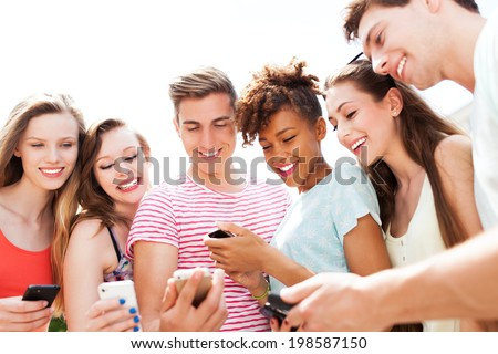 Young people looking at smartphones  - stock photo