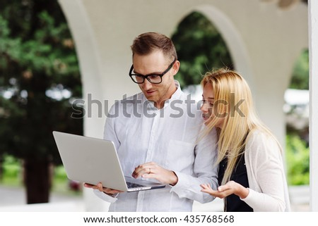 Young people looking on screen of laptop while standing outside.  - stock photo