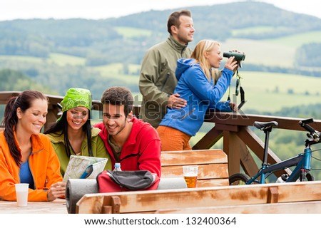 Young people looking through binoculars reading map mountain view holiday - stock photo
