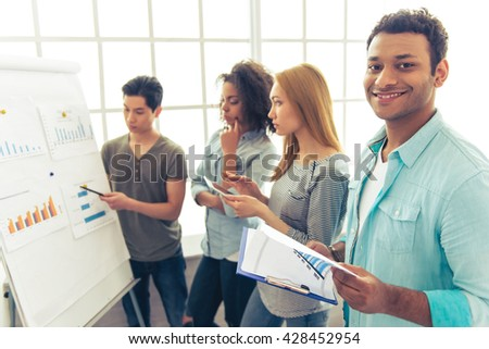 Young people of different nationalities are discussing business affairs while examining graphs. Afro American guy is looking at camera and smiling