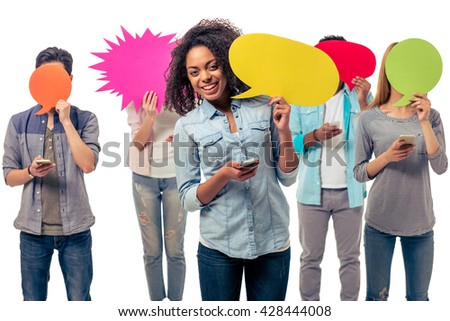 Young people of different nationalities are hiding faces behind speech bubbles while using smartphones, isolated on white background - stock photo