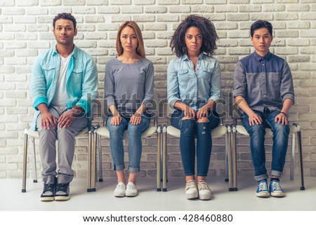 Young people of different nationalities are looking at camera while sitting with hands on knees in a row - stock photo