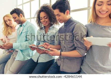 Young people of different nationalities are using gadgets, talking and smiling - stock photo