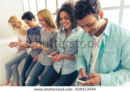 Young people of different nationalities using smartphones and smiling while sitting in a row - stock photo