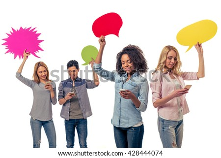 Young people of different nationalities with speech bubbles are using smartphones and smiling, isolated on white background - stock photo