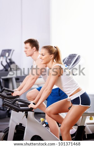 Young people on a bicycle simulator - stock photo