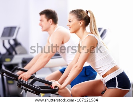 Young people on bikes in a fitness club - stock photo