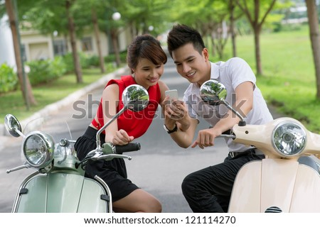 Young people on scooters looking at the screen of a mobile gadget - stock photo