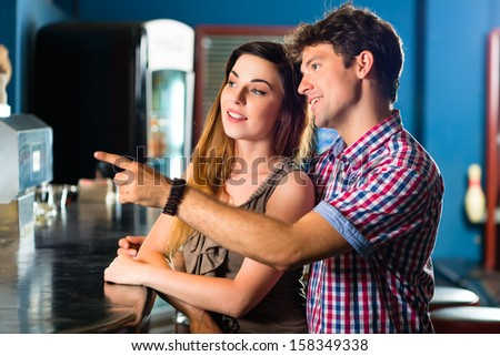 Young people or couple having a date in a club or a bar - stock photo