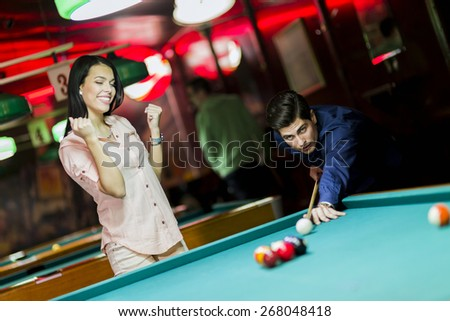 Young people playing billiard in a club pub bar - stock photo
