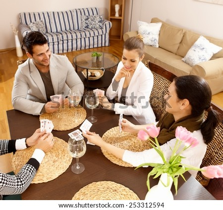 Young people playing cards at home, having fun. - stock photo