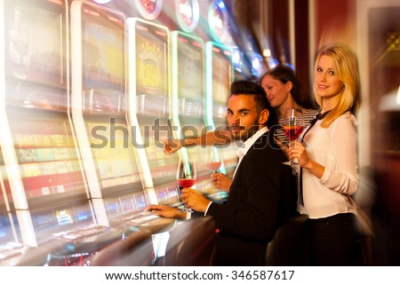 young people playing slot machines in casino