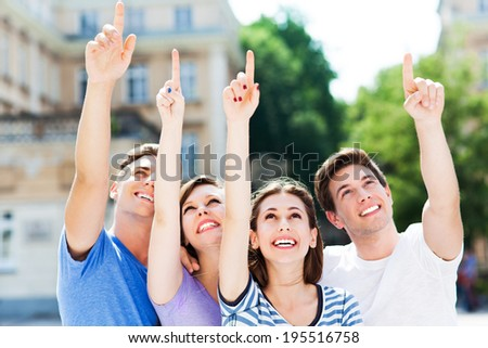 Young people pointing up  - stock photo