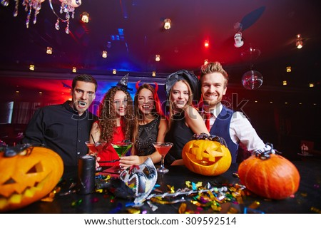 Young people posing in Halloween hats and with pumpkins - stock photo