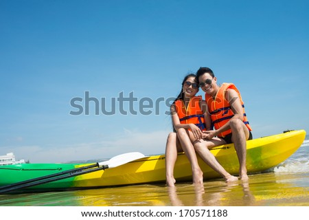 Young people posing in kayak on the sea - stock photo