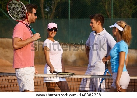 Young people prepared for tennis game, standing on tennis court, smiling.