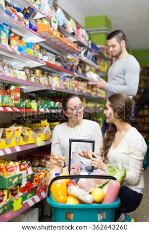 Young people purchasing a food for week at supermarket  - stock photo