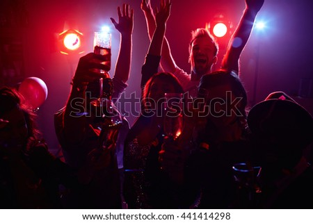 Young people raising their glasses with champagne - stock photo