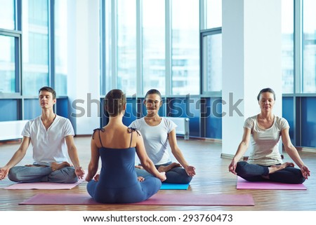 Young people repeating meditation exercise after trainer