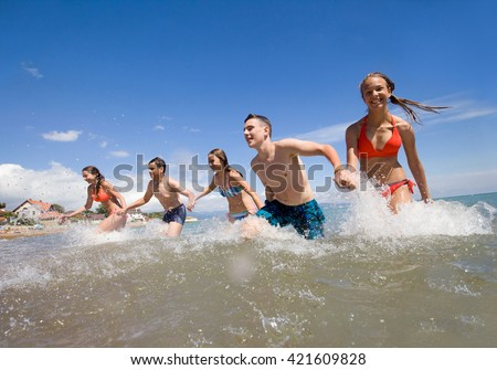 young people running and spraying at the beach on  beautiful summer time - stock photo