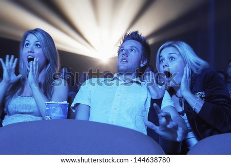 Young people screaming while watching horror movie in the theatre - stock photo