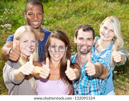 Young people showing thumbs up. - stock photo