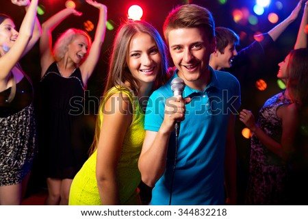 Young people singing into microphone at party - stock photo