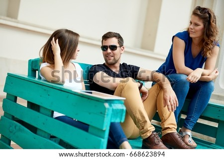 Young people sitting and talking outdoors, sitting on bench.