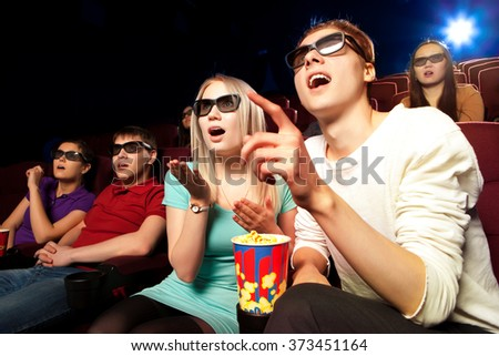 Young people sitting at the cinema, watching a film. Cinema photo series - stock photo