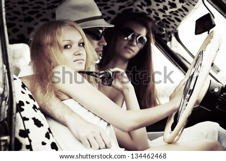 Young people sitting in retro car - stock photo