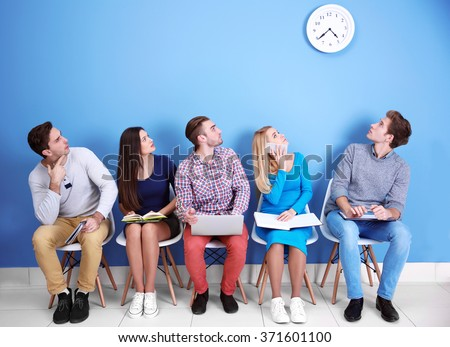 Young people sitting on a chairs and looking at the clock in blue hall - stock photo