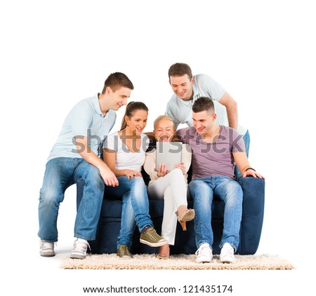 Young people sitting on a sofa, looking at a tablet, on white background - stock photo