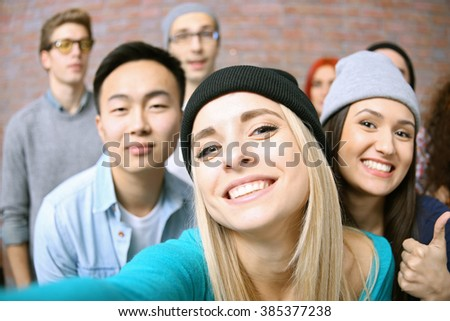 Young people taking group photo on brick wall background - stock photo