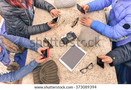 Young people texting and playing with telephone - Group of friends having fun with mobile - Hands holding smartphone - Concept of modern lifestyle and technology - Main focus on tablet and camera - stock photo