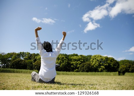 Young people to sit down on the grass - stock photo