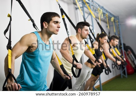 Young people training in elastic rope at fitness gym center