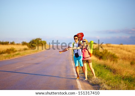 young people traveling hitchhiking. summer road - stock photo