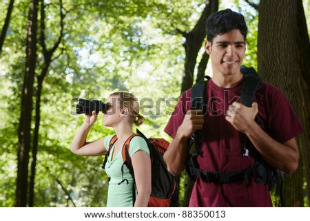 young people trekking among trees and looking at birds with binoculars. Horizontal shape, side view, waist up - stock photo