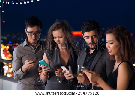 Young people using smartphones instead of socializing at the party: technology addiction - stock photo